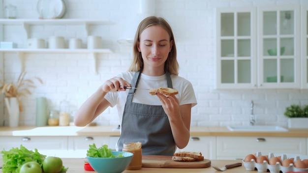 Happy uśmiechnięta kobieta w kuchni przygotowuje kanapkę z masłem orzechowym