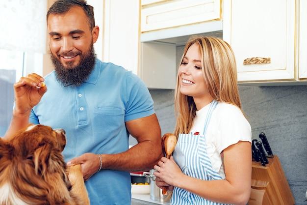 Happy uśmiechnięta para gotowania w kuchni z psem