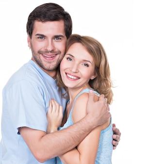 Happy uśmiechnięta para stojących razem patrząc na kamery - na białym tle