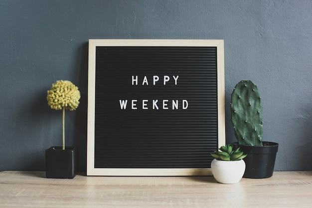 Happy weekend cytat na tablicy z kaktusem, sukulentem i dekoracyjną rośliną na drewnianym stole
