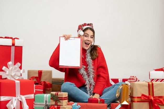Happy xmas dziewczyna z santa hat pokazując dokument siedzi wokół przedstawia na białym tle
