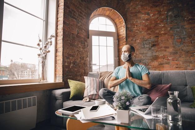 Harmonia. młody mężczyzna robi jogę w domu podczas kwarantanny i pracy online jako freelancer. zdalne biuro, na białym tle. pojęcie zdrowego stylu życia, dobrego samopoczucia, bezpieczeństwa podczas pandemii koronawirusa.