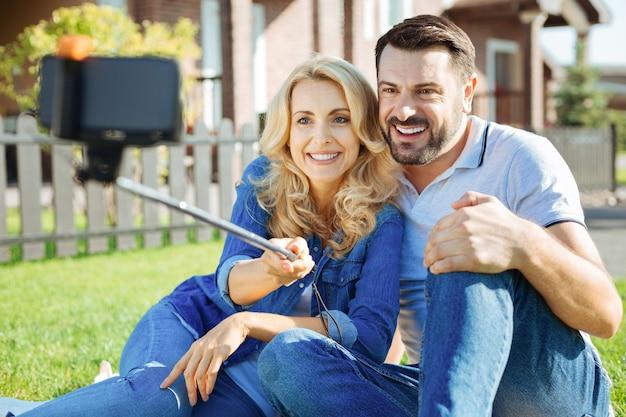 Harmonia rodzinna. wesoła młoda para siedzi na ziemi na swoim podwórku i robi selfie razem z kijem do selfie, uśmiechając się radośnie do kamery