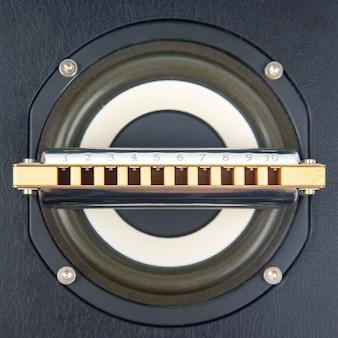 Harmonijka ustna leży na głośniku audio. klasyczny muzyczny instrument dęty.