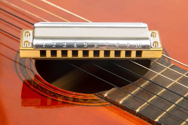Harmonijka ustna spoczywa na korpusie gitary klasycznej. klasyczny muzyczny instrument dęty.