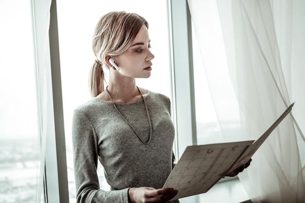 Harmonogramy dla pracowników. udana bizneswoman trzyma jakieś dokumenty z harmonogramami dla pracowników