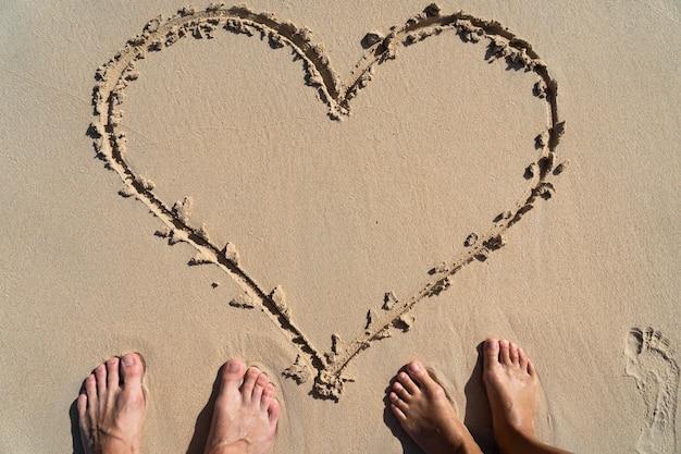 Hart na piasku ze stopami pary, symbol miłości. pojęcie relacji i wspólnoty.
