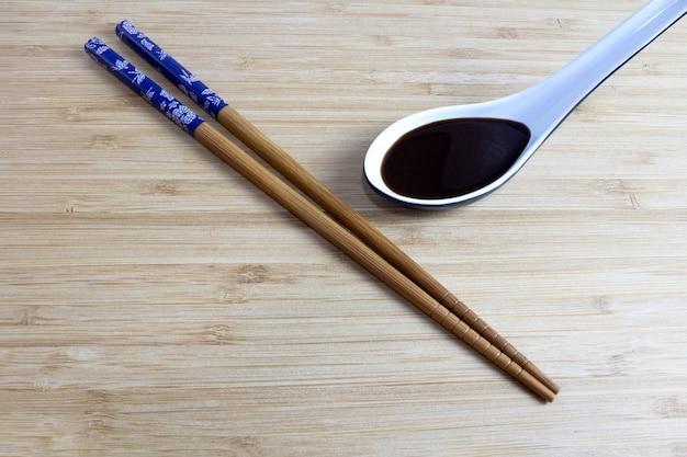 Hashi na bambusowym stole i sos sojowy z boku