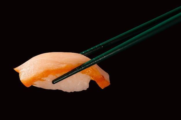 Hashi trzymać sushi i rolki odizolowane na czarnym tle