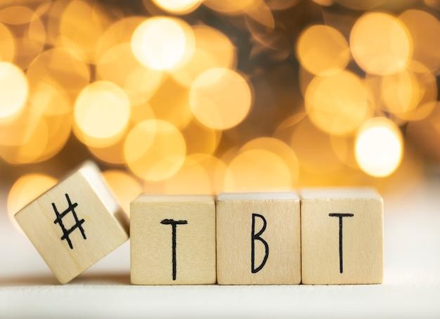 Hashtag tbt powrót w czwartek napisany drewnianymi kostkami z błyszczącym tłem bokeh, kolorowa koncepcja mediów społecznościowych