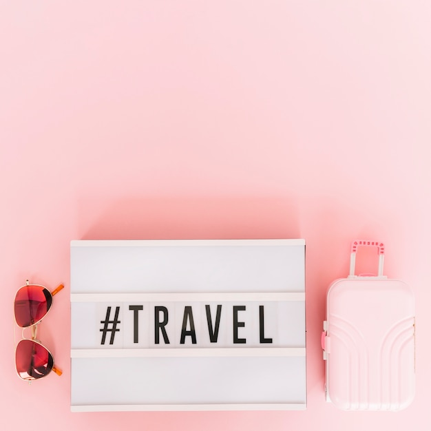 Hashtag z tekstem podróży na lightboxie z okularami przeciwsłonecznymi i miniaturową torbą podróżną na różowym tle