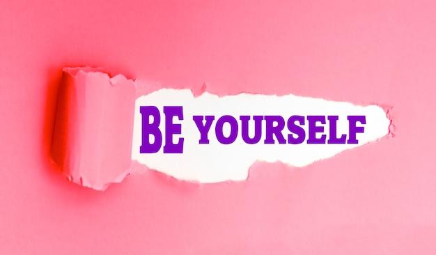 Hasło be yourself na podartym różowym papierze