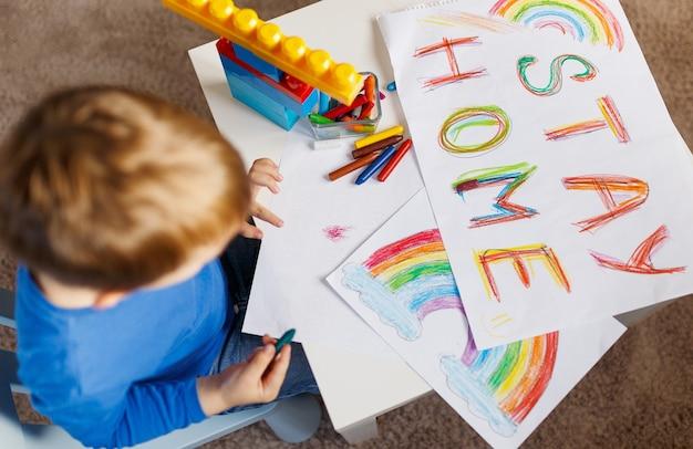 Hasło związane z pandemią koronawirusa zostań w domu. chłopiec kaukaski rysuje dom i słowo zostań w domu na papierze ołówkiem. wezwać do samoizolacji w przypadku pandemii koronawirusa i nie wychodzenia z domu na ulicę. widok z góry