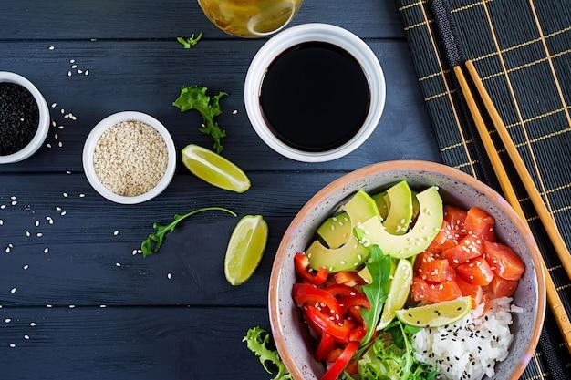Hawajska łosoś miska z ryżem, awokado, papryką, sezamem i limonką.