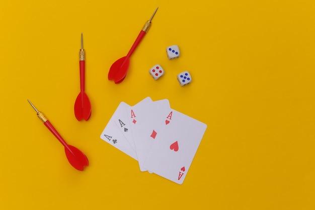 Hazard. cztery asy, kości i rzutki na żółtym tle. widok z góry