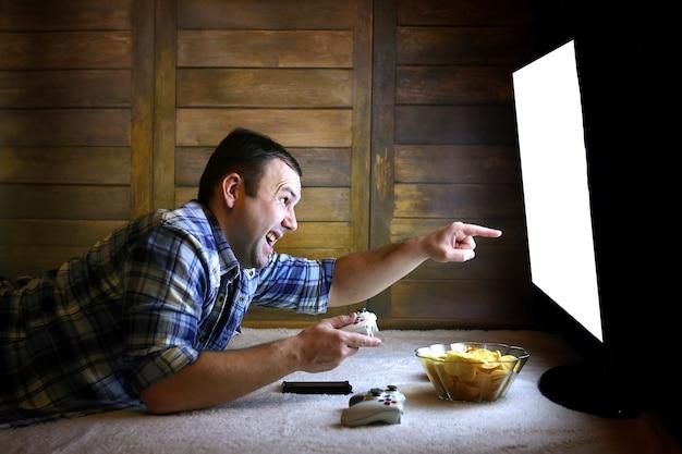 Hazardzista grający na konsoli na joysticku przed dużym ekranem telewizora
