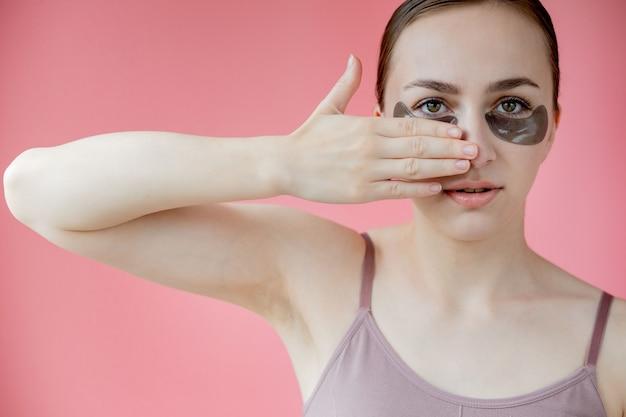 Head shot portret z bliska uśmiechnięta młoda kobieta z maską pod oczy nawilżające plastry lookin