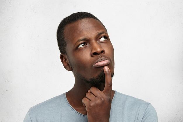 Headshot atrakcyjnego młodego ciemnoskórego mężczyzny ubranego niedbale patrząc w górę