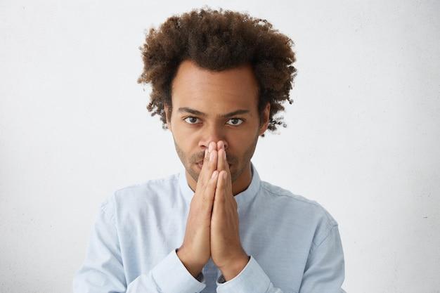 Headshot atrakcyjnego pracownika afro american z ostrą fryzurą trzymającą się za ręce na twarzy