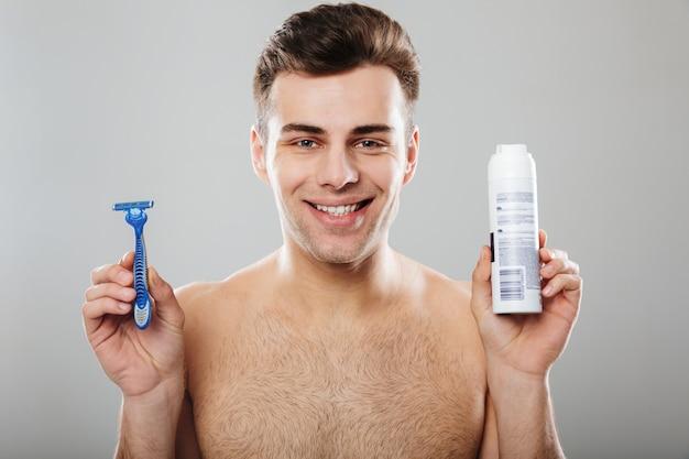 Headshot brunetka szczęśliwy facet 30s rozbiera się w łazience trzymając brzytwę i krem do golenia na szarej ścianie
