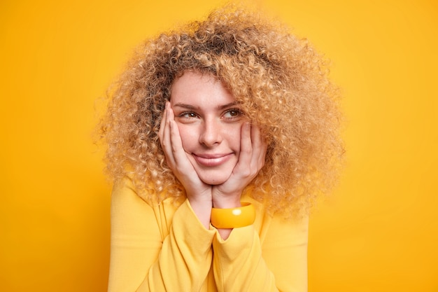 Headshot całkiem pięknej młodej europejki ma rozmarzony wyraz twarzy trzyma ręce na policzkach, o czym myśli