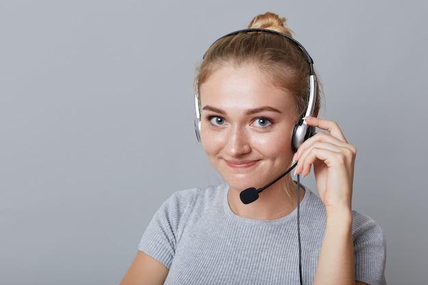 Headshot całkiem uroczej kobiety używa słuchawek z mikrofonem