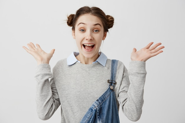 Headshot energiczna kobieta z fryzury odango stojący z rękami do góry, wyrażając niespodziankę. uśmiechnięta kobieta 20s gestykuluje krzyczeć z radości i oczy pełne szczęścia. wyrazy twarzy