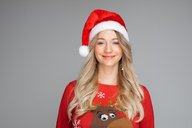 Headshot młoda ładna blond tysiącletnia dziewczyna kaukaski w santa hat i ciepły zimowy sweter bożonarodzeniowy, portret studio