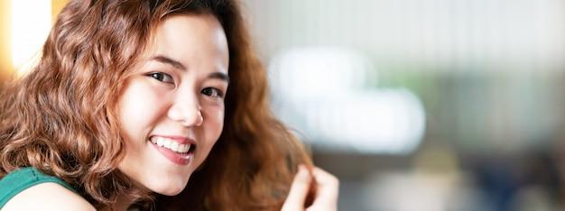 Headshot młodych szczęśliwych atrakcyjnych azjatyckich z modnymi kręconymi włosami brunetka stylowy projektant kobiet lub influencer uśmiechnięty i patrząc na kamery z pewnością siebie i pozytywnie. portret azjatykcia śliczna dziewczyna.