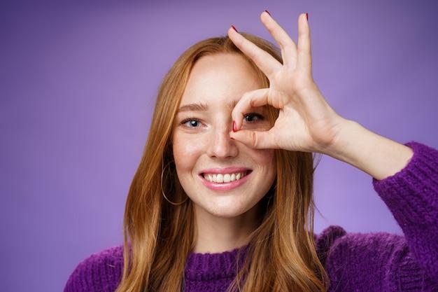 Headshot optymistycznej i zabawnej, miłej, uroczej rudowłosej kobiety z piegami i białym idealnym uśmiechem pokazującym znak porządku lub zero na oku, uśmiechając się, jak zerkając przez otwór w aparacie na fioletowym tle.