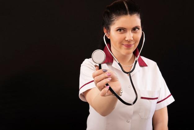 Headshot portret lekarza pielęgniarki w mundurze ze stetoskopem, na białym tle na ciemnym tle, kopia przestrzeń