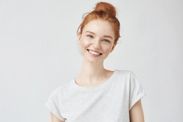 Headshot portret szczęśliwa imbirowa kobieta z piegami uśmiecha się biel.