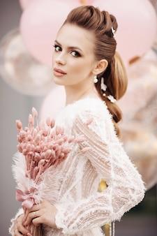 Headshot przepięknej brunetki z nieskazitelną skórą, wysoką fryzurą, profesjonalnym makijażem i bukietem różowych kwiatów, patrząc na kamery. nieostre różowe tło.