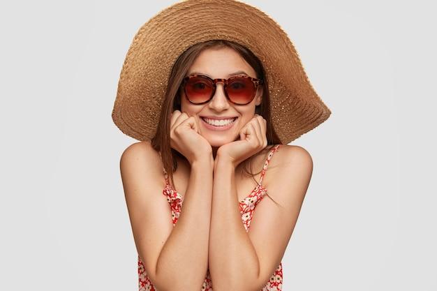 Headshot przyjemnie wyglądającej uśmiechniętej kobiety trzyma obie ręce pod brodą