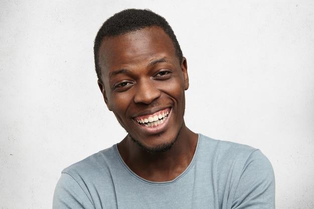 Headshot przystojny, emocjonalny, młody, afroamerykański mężczyzna z wesołym szczęśliwym uśmiechem