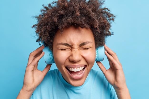 Headshot rozradowanej afro amerykanki z kręconymi, krzaczastymi włosami, śmieje się radośnie w bezprzewodowych słuchawkach, słucha ulubionej melodii lub ścieżki dźwiękowej, ubranej swobodnie, odizolowanej na niebieskiej ścianie.