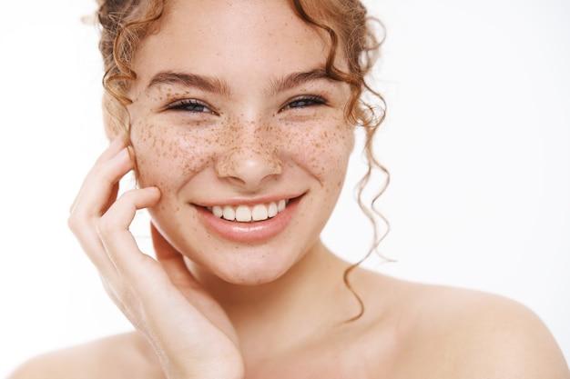 Headshot szczęśliwa delikatna ruda dziewczyna piegi uśmiechając się szeroko białe zęby stojąc nago delikatnie dotykając policzka dbanie o ciało pod prysznicem, stosowanie kosmetyków pielęgnacyjnych do pielęgnacji skóry, codzienna procedura higieny