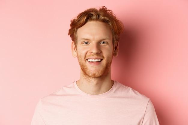 Headshot szczęśliwy rudy mężczyzna z brodą i białymi zębami, uśmiechnięty podekscytowany do kamery, stojący na różowym tle.