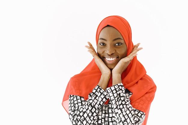 Headshot uroczej, zadowolonej religijnej muzułmanki o delikatnym uśmiechu, o ciemnej, zdrowej skórze, noszącej szalik na głowie. pojedynczo na białym tle.