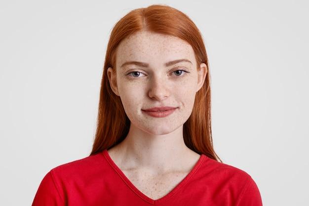 Headshot z dość piegowatą rudowłosą kobietą z przyjaznym wyrazem twarzy przed kamerą