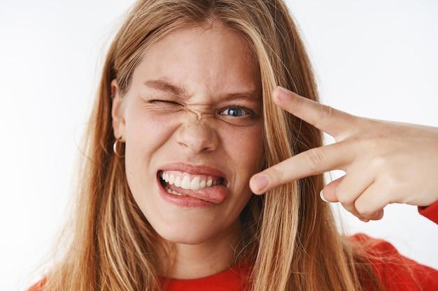 Headshot zabawnej, emocjonalnej i charyzmatycznej młodej beztroskiej kobiety, która robi miny wystające język pokazujący gest pokoju i mrugające, wyrażające pozytywne i podekscytowane emocje pozujące nad szarą ścianą