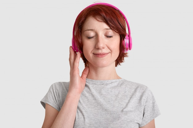 Headshot zadowolonej młodej kobiety nosi słuchawki, słucha ulubionej muzyki, zamyka oczy z przyjemności, cieszy się głośnym dźwiękiem, ubrany w swobodną koszulkę, izolowaną na białej ścianie. koncepcja hobby