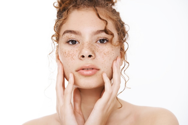 Headshot zmysłowa delikatna ruda kobieta z kręconymi włosami piegi stojąca nago białe tło dotykając czysta czysta skóra wygląd lustro stosując produkty do pielęgnacji skóry kosmetyki, białe tło