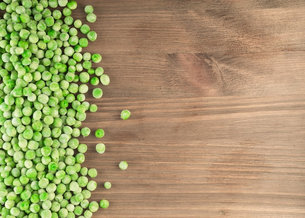 Heap of frozen sweet green peas on wooden table top view with copyspace