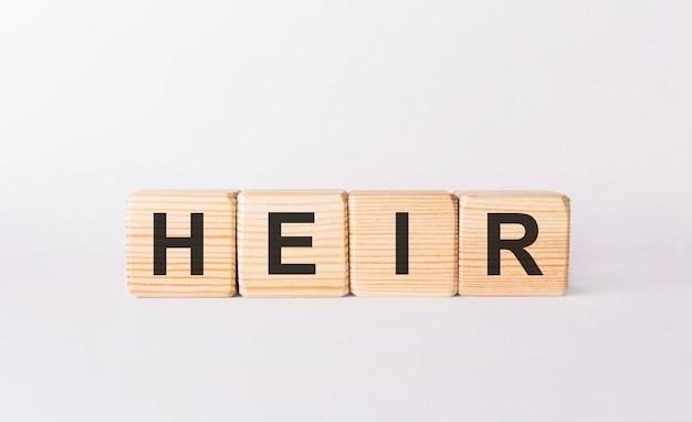 Heir słowo wykonane z drewnianych klocków na białym tle
