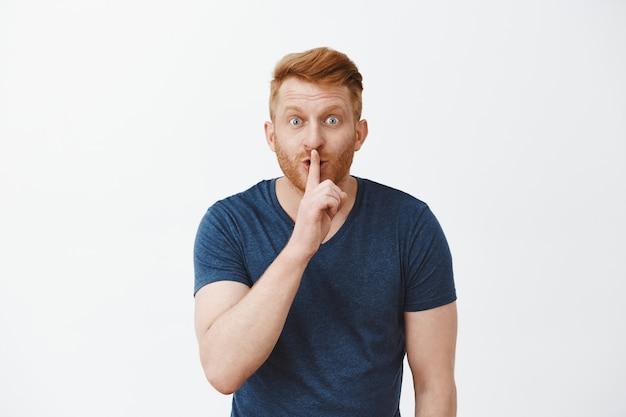 Hej, chcesz usłyszeć mój sekret. przystojny, entuzjastyczny rudy, nieogolony męski model jest zachwycony wspaniałymi wiadomościami, mówi cii, pokazując gest uciszenia, chcąc zrobić niespodziankę