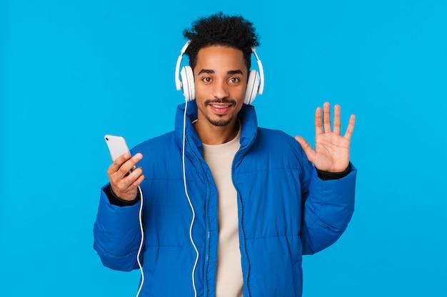Hej, miło cię widzieć. wesoły, stylowy, afroamerykański mężczyzna w wyściełanej kurtce zimowej, słuchaj słuchawek muzycznych, przytrzymaj piosenkę przełącznika telefonu,