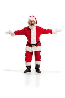 Hej, witam. holly jolly x mas festive noel. pełna długość zabawnego szczęśliwego mikołaja w nakryciu głowy, kostiumie, czarnym pasku, białych rękawiczkach, falach z dłonią stojącą w studio na białym tle