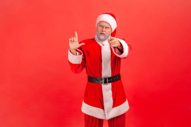 Hej, zawiodłeś! święty mikołaj pokazujący gest przegranego, wskazujący na kamerę, oskarżający o pomyłkę