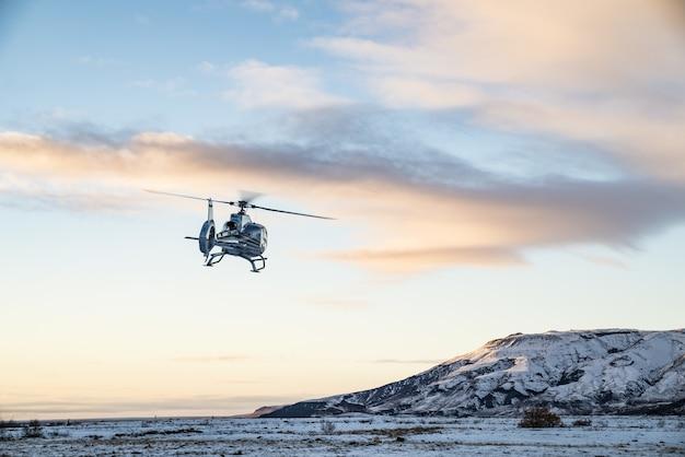 Helikopter leci nad pokrytą śniegiem tundrą
